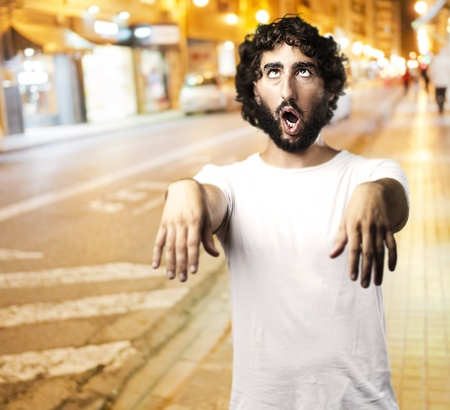 Young man imitating a zombie against a city at night background photo