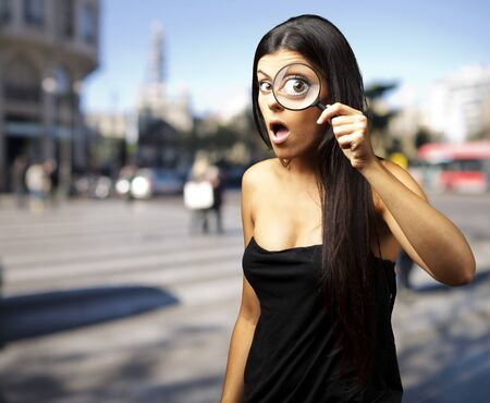 investigators: Young woman surprised looking through a magnifying glass at city