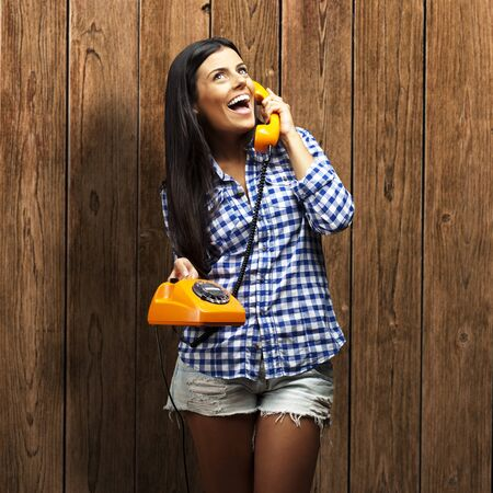 portrait of young woman talking on vintage telephone against a wooden wall Stock Photo - 15856936