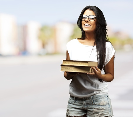 portrait of young girl holding books at crowded city photo