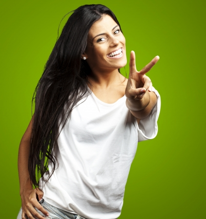 Happy Young Woman Showing Victory Sign On Green Background photo