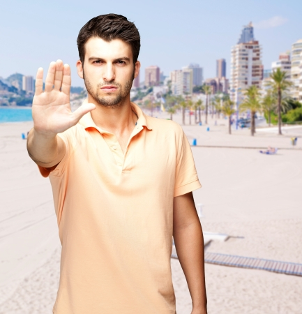 portrait of a handsome young man doing stop symbol against a beach Stock Photo - 15852848
