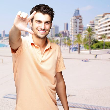 portrait of a handsome young man doing good symbol against a beach photo