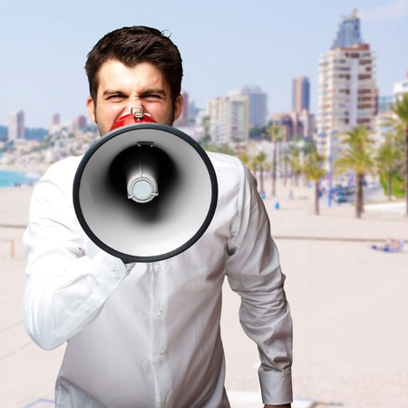portrait of young man screaming with megaphone against a beach photo