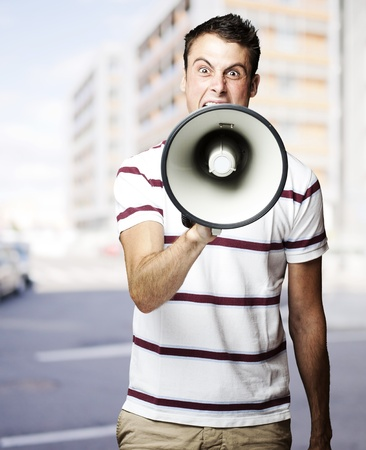 inform: portrait of young man shouting with megaphone at city Stock Photo