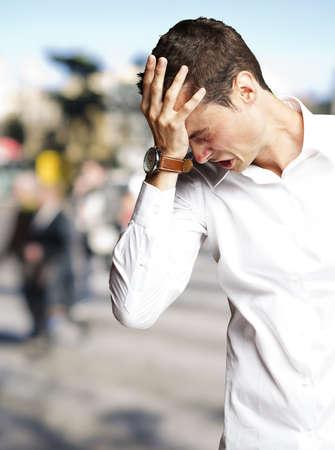 Angry young man doing frustration gesture at crowded place Stock Photo - 15850591