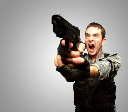 Angry Soldier Man With Gun Isolated On gray Background photo