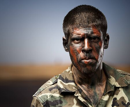young soldier with camouflage paint looking very serious against a desert Stock Photo - 15853766