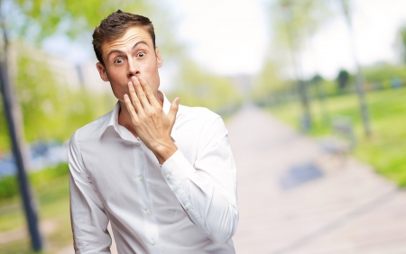 outraged: Portrait Of Young Man Covering His Mouth With Hand, Outdoor Stock Photo