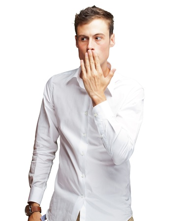 Portrait Of Young Man Covering His Mouth With Hand On White Background photo