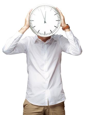 Jeune homme tenant grande horloge couvrant son visage sur fond blanc
