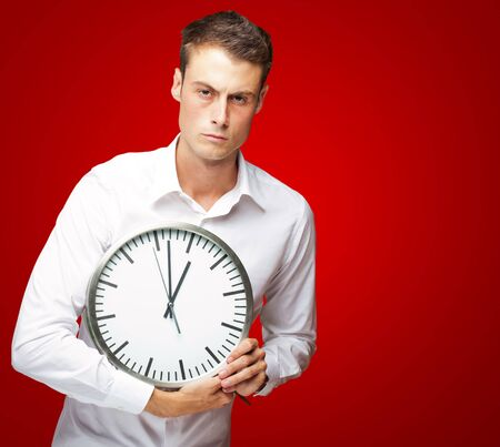 Angry Man Holding Clock In His Hand On Red Background photo