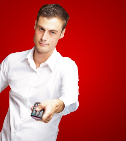 Man Holding Remote In His Hand On Red Background photo