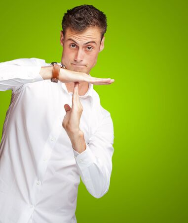 Portrait Of Young Man Gesturing Time Out Sign On Green Background Stock Photo - 15851207