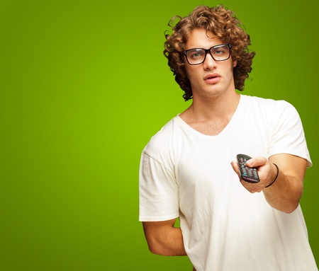 out of control: Man Holding Remote Control Isolated On Green Background