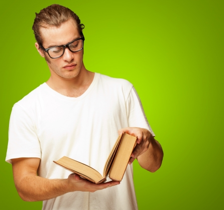 Man Looking At Book On Green Background photo