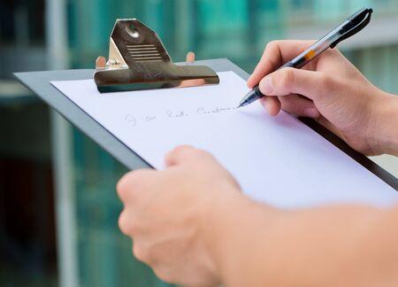 revisando documentos: Hombre de negocios que sostiene un sujetapapeles y la escritura, Out Door Foto de archivo