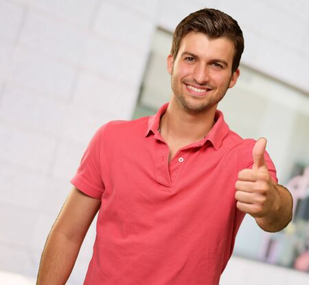 young man smiling with thumbs up, indoor photo