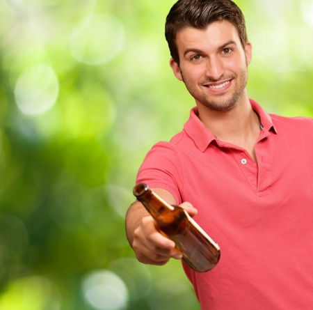 young man holding a beer, outdoor photo