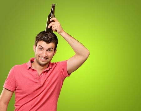 botellas vacias: Retrato de hombre joven sosteniendo la botella en la cabeza en fondo verde Foto de archivo