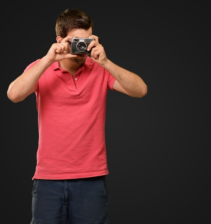 Portrait of a man taking photo on black background photo