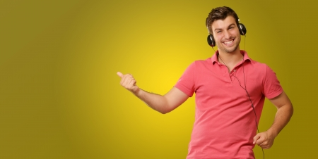 listen fist: Young man wearing headphones isolated on yellow background Stock Photo