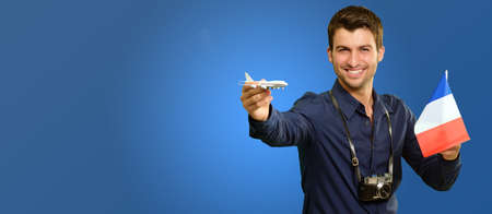 Man Holding A Miniature Airplane And France Flag On Blue Background photo