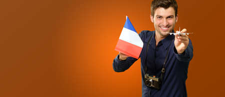 Man Holding A Miniature Airplane And France Flag On Coloured Background photo