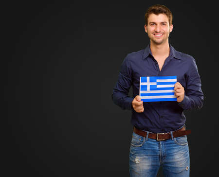 A Young Man Holding A Greece Flag On Black Background photo
