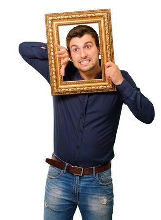 clenching: A Young Man Holding And Looking Through Frame On White Background