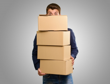 relocate: Man holding cardboard boxes on grey background