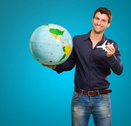 A Young Man Holding A Globe And Miniature Airplane On Blue Background photo