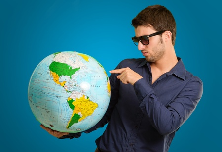 A Young Pointing On A Globe On Blue Background photo