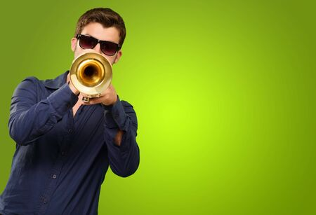 young musician: A Young Man Blowing A Trumpet On Green Background Stock Photo