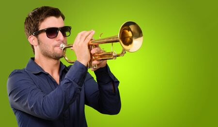 trumpeter: A Young Man Blowing A Trumpet On Green Background Stock Photo