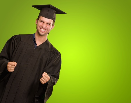 Young Man In Graduation Gown On Green Background photo
