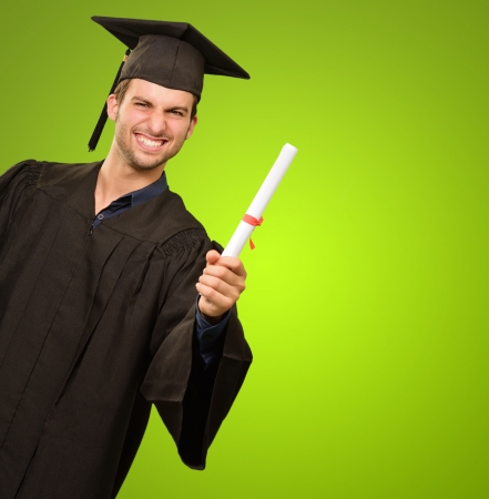 Young Man In Graduation Gown Holding Certificate On Green Background photo