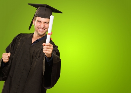 Young Man In Graduation Gown Holding Certificate On Green Background Standard-Bild