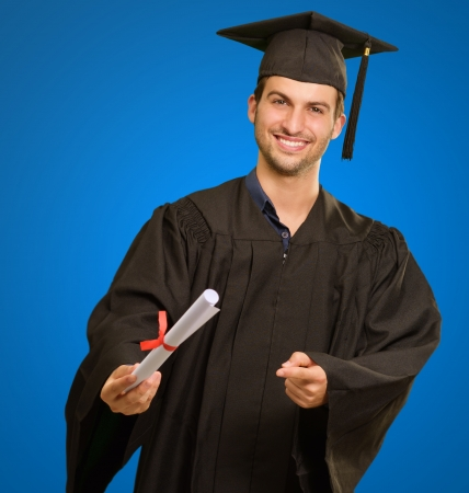 Young Man In Graduation Gown Holding Certificate On Blue Background photo