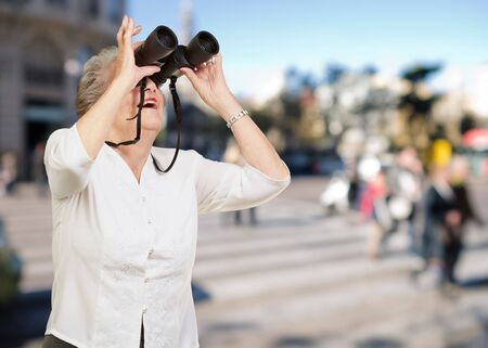 portrait of senior woman looking through a binoculars at crowded street photo