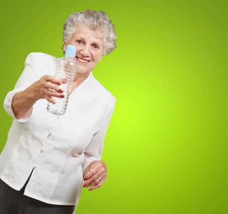 portrait of healthy senior woman holding a water bottle over green background photo