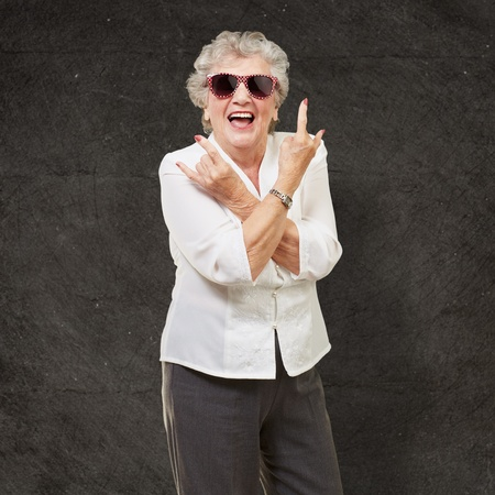 seniority: Senior woman wearing sunglasses doing funky action isolated on black background