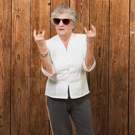 damas antiguas: La mujer mayor con gafas de sol que hacen acción cobarde, de interior