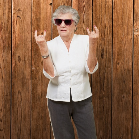 funny glasses: Senior woman wearing sunglasses doing funky action, indoor Stock Photo
