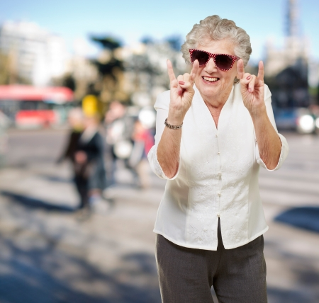 portrait of a happy senior woman doing rock symbol at crowded street Stock Photo - 15855558