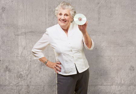 Senior woman holding cd, indoor photo