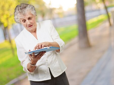 Senior woman using tablet, outdoor photo