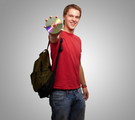 Portrait Of A Student Holding A Compact Disk On Gray Background photo