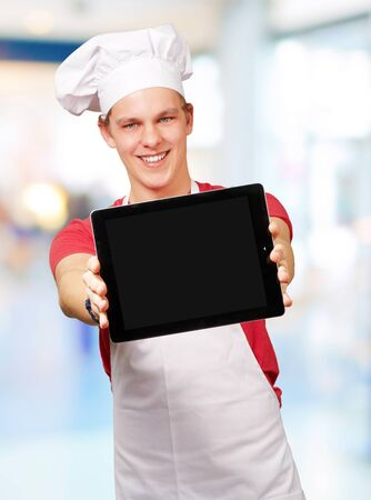 portrait of young cook man showing a digital tablet indoor photo