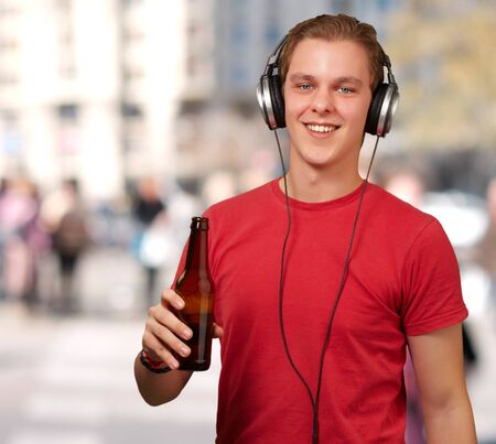 portrait of young man listening music and holding beer against a building photo